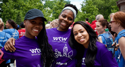 Three female Informa colleagues in purple Walk the World t-shirts at Informa's annual charity walk