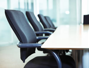 Four empty office chairs line up at a boardroom table