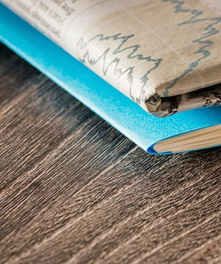 Close up of the corner of a folded newspaper and the corner of a blue paper folder, on top of a wooden table